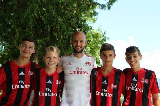 Quatro meninos com seu instrutor no acampamento de verão do AC Milan Academy