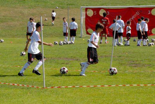 男孩和女孩在AC米兰足球营提高他们的运球技能